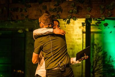 employee-recognition-hug-on-stage