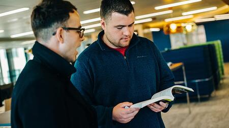 two-male-employees-talking-reading-book