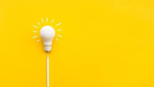 RG4SB_white_idea_lightbulb_with_white_pencil_on_yellow_background